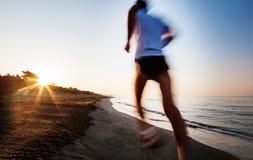 Spring för ung man på en strand på soluppgång Effekt för rörelsesuddighet arkivfoto