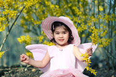 Spring fairy3. Two year old girl dressed as fairy enjoying spring flowers Stock Photo