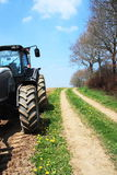 Spring Farm Lane And Tractor Stock Photo