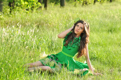 Spring fashion. A beautiful girl with a green dress si resting a little..it's spring time and everithing is green..including the dress stock image