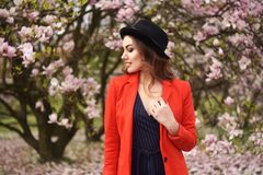 Spring fashion girl outdoors portrait in blooming trees. Beauty Romantic woman in flowers. Sensual Lady enjoying Nature. stock photo