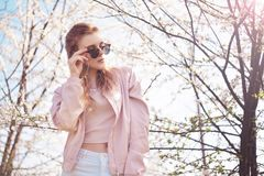 Spring fashion girl outdoors portrait in blooming trees. Beauty Romantic woman in flowers in sunglasses. Sensual Lady. Beautiful Woman Enjoying Spring Nature royalty free stock images