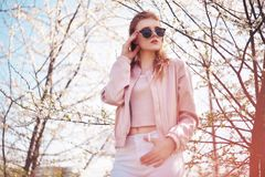 Spring fashion girl outdoors portrait in blooming trees. Beauty Romantic woman in flowers in sunglasses. Sensual Lady. royalty free stock photos