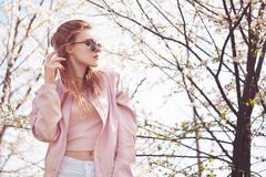 Spring fashion girl outdoors portrait in blooming trees. Beauty Romantic woman in flowers in sunglasses. Sensual Lady. royalty free stock image