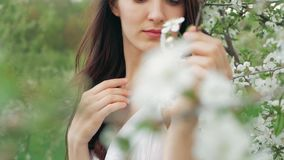 Spring fashion portrait of a beautiful happy young woman in white dress with long brown hair run and enjoy smell flowers. Spring fashion portrait of a beautiful stock video
