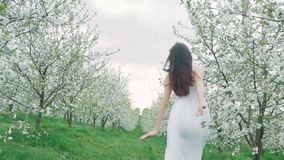 Spring fashion portrait of a beautiful happy young woman in white dress with long brown hair run and enjoy the. Blossoming garden stock video