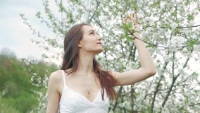 Spring fashion portrait of a beautiful happy young woman in white dress with long brown hair run and enjoy smell flowers. In the blossoming garden stock video