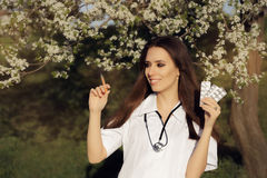 Spring Female Doctor Deciding with  Vaccine Syringe and Pills Stock Image