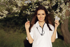 Spring Female Doctor Deciding with  Vaccine Syringe and Pills Stock Photo