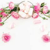 Spring feminine composition with pink roses and marshmallow on white background. Top view. Flat lay. Spring feminine composition with pink roses and marshmallow Stock Photos