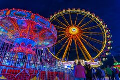 Spring Festival in Munich at the blue hour with a lightened ferris wheel and chain carusel. stock photos
