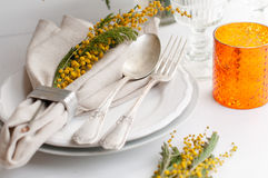 Spring festive dining table setting. With yellow mimosa flowers, candles, napkins and vintage cutlery on a white wooden board Royalty Free Stock Photos