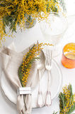 Spring festive dining table setting. With yellow mimosa flowers, candles, napkins and vintage cutlery on a white wooden board Royalty Free Stock Images