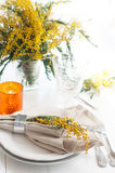 Spring festive dining table setting. With yellow mimosa flowers, candles, napkins and vintage cutlery on a white wooden board Stock Photos