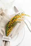 Spring festive dining table setting. With yellow mimosa flowers, candles, napkins and vintage cutlery on a white wooden board Stock Photography