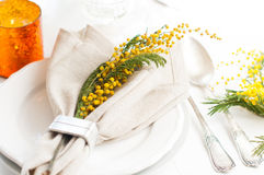 Spring festive dining table setting. With yellow mimosa flowers, candles, napkins and vintage cutlery on a white wooden board Royalty Free Stock Photo