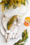 Spring festive dining table setting. With yellow mimosa flowers, candles, napkins and vintage cutlery on a white wooden board Stock Images