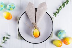 Spring festive Easter table setting with bunny ears linen napkin and kitchen cutlery. Flat lay, stock photography