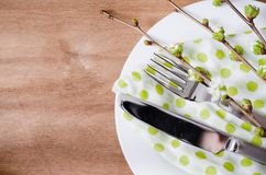 Spring Festive Table Setting with Cutlery. Spring Festive Table Setting with Flowering Branch Cherries, Cutlery and Napkin on Wooden Rustic Table. Selective Royalty Free Stock Photos