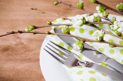 Spring Festive Table Setting with Cutlery. Spring Festive Table Setting with Flowering Branch Cherries, Cutlery and Napkin on Wooden Rustic Table. Selective Stock Photo