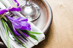 Spring festive table setting with fresh flower. Napkin, plate and cutlery on wooden table. Holidays background. Selective Focus Stock Photography