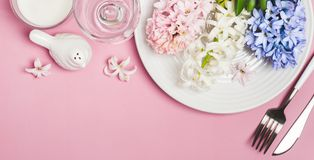Spring festive Table setting with hyacinth flowers on a pink background.  Royalty Free Stock Photo