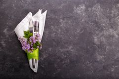 Spring festive table setting. With cutlery and lilac flowers on black stone table,copy space flat lay Royalty Free Stock Photos
