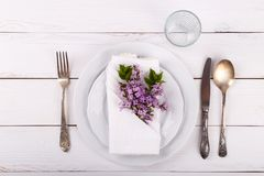 Spring festive table setting. With vintage cutlery and lilac flowers on white wooden table,copy space flat lay Royalty Free Stock Image