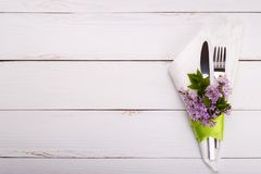 Spring festive table setting. With vintage cutlery and lilac flowers on white wooden table,copy space flat lay Stock Photo