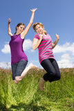 Spring fever. Two young women jumping around on a meadow Stock Image