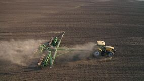 Spring field work, a tractor with a mounted seeder sow seeds in the ground on an agricultural field