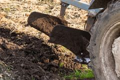 Spring field work tractor stands on a field dumped with manure with raised plows royalty free stock photos