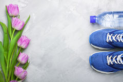 Spring flatlay composition with sneakers and tulips. Spring flatlay sports composition with blue sneakers, bottle of water and Royalty Free Stock Photos