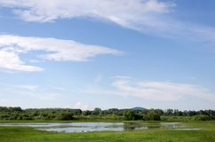 Spring flooding. Flood basin of the Tisza River in Tiszalok, Hungary. Hungarian countryside. Overflow of water from the river. Blue sky. Tokaj Hill and a TV stock photo