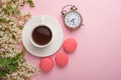 Spring floral background with coffee and macaroons, and alarm clock. Flat white flowers on a light pink background, top view, copy stock photo