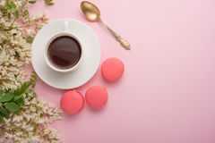Spring floral background with coffee and macaroons, textures and wallpaper. Flat white flowers on a light pink background, top vie stock images