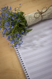 Spring floral bouquet of forget-me-and a notebook for notes on a Stock Photo
