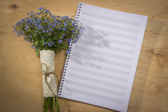 Spring floral bouquet of forget-me-and a notebook for notes on a Royalty Free Stock Photos