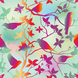 Spring floral seamless wallpaper with birds on branches over blue sky Stock Images