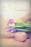 Spring flower arrangement against a rustic background Stock Images
