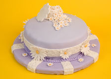 Spring Flower Cake. A spring-fresh fondant-covered cake, decorated with daisies both large and small, sits isolated on yellow Stock Photography