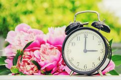 Spring flowers and Alarm Clock. Change the time. Selective focus stock image