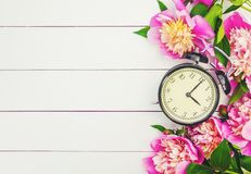 Spring flowers and Alarm Clock. Change the time. Selective focus stock images