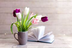 Free Spring Flowers And Book At Wooden Background. Tulips In Gray Cup. Bouquet In Vase. Stock Photo - 189620680
