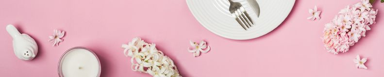 Spring flowers banner. Hyacinths and tableware on a pink background.  royalty free stock photography
