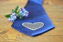 Spring flowers and blue tie on wooden background Stock Images