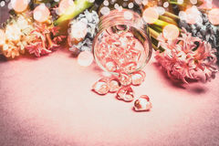 Spring flowers border with bokeh and glass hearts decoration on pink background Stock Photos
