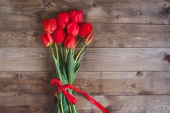 Spring flowers. Bouquet of Red tulips on brown wooden background. Stock Photography
