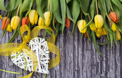 Spring flowers bouquet of yellow and red tulips and daffodils on a gray background with the motif of the wall and brick with white Stock Images