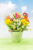 Spring flowers in a bucket. A bunch of spring flowers in a metal bucket in a artificial landscape Stock Photography